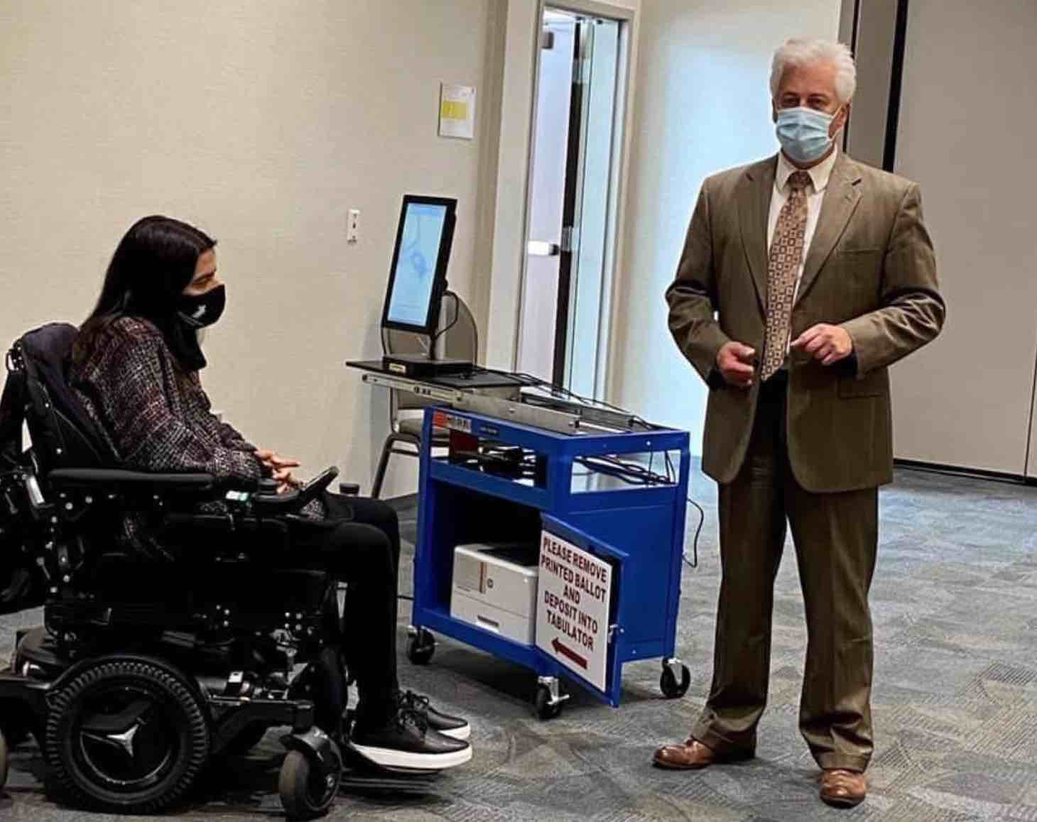 picture of woman using wheelchair and man standing at a voting station