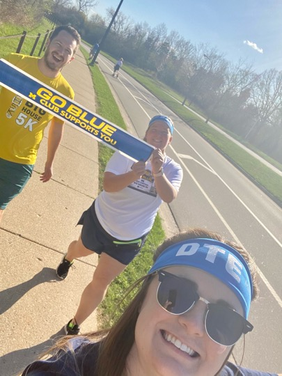 3 people running holding go blue sign